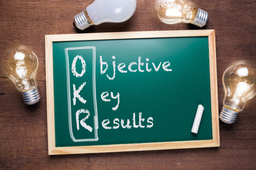 OKR or Objective Key Results acronym text on chalkboard with many glowing light bulbs, washington dc, crosslead